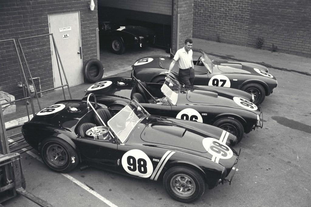 Caroll Shelby posiert mit seinen drei Cobra Roadster